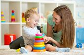 stock photo of indoor games  - cute mother and child boy playing together indoor at home - JPG