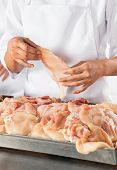 Midsection of female butcher holding meat piece in butchery