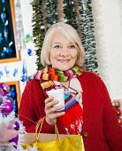 Beautiful senior woman with shopping bags and coffee cup standing at Christmas store