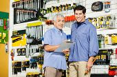 Portrait of happy father and son with clipboard in hardware store