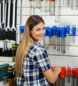 Side view portrait of female customer selecting screwdriver in hardware shop