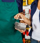 Female customer paying with smartphone using NFC technology in hardware store