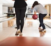 Rear view of young women playing in bowling alley
