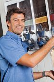 Portrait of male customer standing by coffee vending machine in supermarket