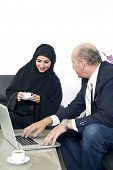 Senior Businessman working with Arabian Businesswoman wearing hijab
