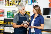 Senior salesman holding electronic reader while female customer paying through smartphone in hardware store
