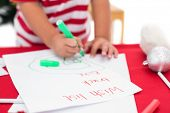 Festive little boy writing wish list on white background