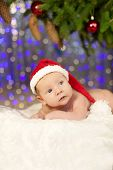 Christmas newborn baby in santa hat. Winter child on winter wonderland background of blurred lights