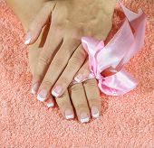 French manicure with pink and red hearts on the nails.