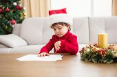 Festive little boy writing wish list at home in the living room