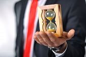 image of hourglass figure  - Man in a suit with tie holding an hourglass
