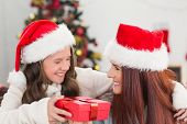 Festive mother and daughter smiling at each other at home in the living room