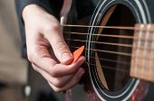 Female hand playing acoustic guitar.guitar play.Close up of guitarist hand playing acoustic guitar
