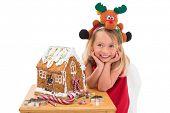 Festive little girl making gingerbread house on white background