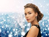 people, holidays, christmas and glamour concept - beautiful woman in evening dress wearing earrings over snowy background