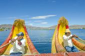 PUNO, PERU, MAY 5, 2014: Uros islands on Titicaca lake - Local men in traditional attire row