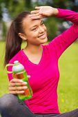 fitness, park, drink and sport concept - smiling african american woman sitting and holding bottle outdoors