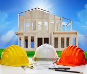 stock photo of structural engineering  - hard hat of engineering on working table with plan and writing tool against house structure in construction - JPG