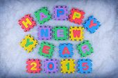 stock photo of time-piece  - Happy New Year 2015 sign made out of alphabet and numbers puzzle pieces isolated on icy background - JPG