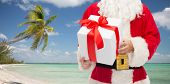 christmas, holidays, travel and people concept - close up of santa claus with gift box over tropical beach background