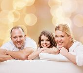 family, childhood, holidays and people - smiling mother, father and little girl over beige lights background