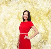christmas, holidays, valentine's day, celebration and people concept - smiling woman in red dress over yellow lights background