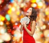 christmas, holidays, sale, banking and people concept - smiling woman in red dress with us dollar money over red lights background