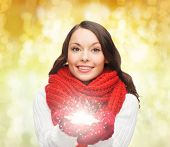 happiness, winter holidays, christmas and people concept - smiling young woman in red scarf and mittens holding snowflake over yello lights background
