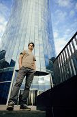 young man stand in front of modern business building