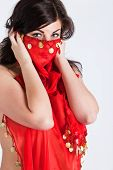 Beautiful Young Woman Covering Her Face And Body In Red Oriental Shawl