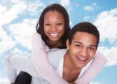 foto of piggyback ride  - Portrait of happy young man giving piggyback ride to woman against sky - JPG