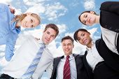 foto of huddle  - Low angle portrait of multiethnic business people forming huddle against sky - JPG