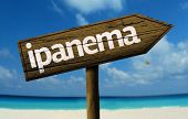 Ipanema, Brazil wooden sign with a beach on background