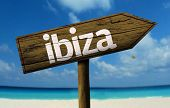 Ibiza, Spain wooden sign with a beach on background