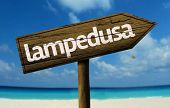 Lampedusa, Italy wooden sign with a beach on background