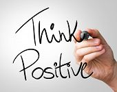 Think Positive hand writing with a black mark on a transparent board