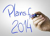 Plans for 2014 hand writing with a blue mark on a transparent board