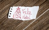 Feliz Natal (Merry Christmas) written on the paper on a wood background