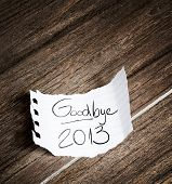 picture of reveillon  - Goodbye 2013 written on the paper on a wood background - JPG