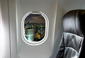Buildings through aircraft window onto jet engine at night