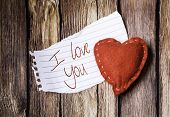 I Love You written on a peace of paper and a heart on a wooden background