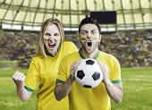 Brazilian fans celebrate on the stadium with their faces painted