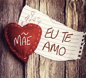 "foto of miss you  - ""Mae, Te Amo"" (In portuguese - Mother, I Love You) written on a peace of paper and a heart on a wooden background - JPG"