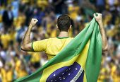 Brazilian soccer player holding the flag of Brazil celebrates on the stadium