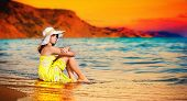 beautiful young brunette girl with hat sitting on the beach in a yellow dress. Cute teen girl