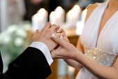 Bride Putting A Ring On Groom's Finger