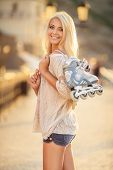 picture of inline skating  - Blonde girl puts on skates for skating through the streets of the spa town in the summer - JPG