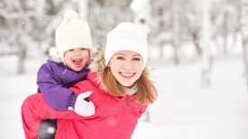 picture of mother baby nature  - happy family mother and baby girl daughter playing and laughing in winter outdoors in the snow - JPG