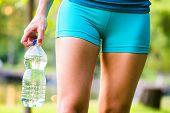 image of bottle water  - Sporty woman holding bottled water after exercising - JPG