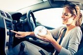 stock photo of designated driver  - Young female driver playing music in the car  - JPG
